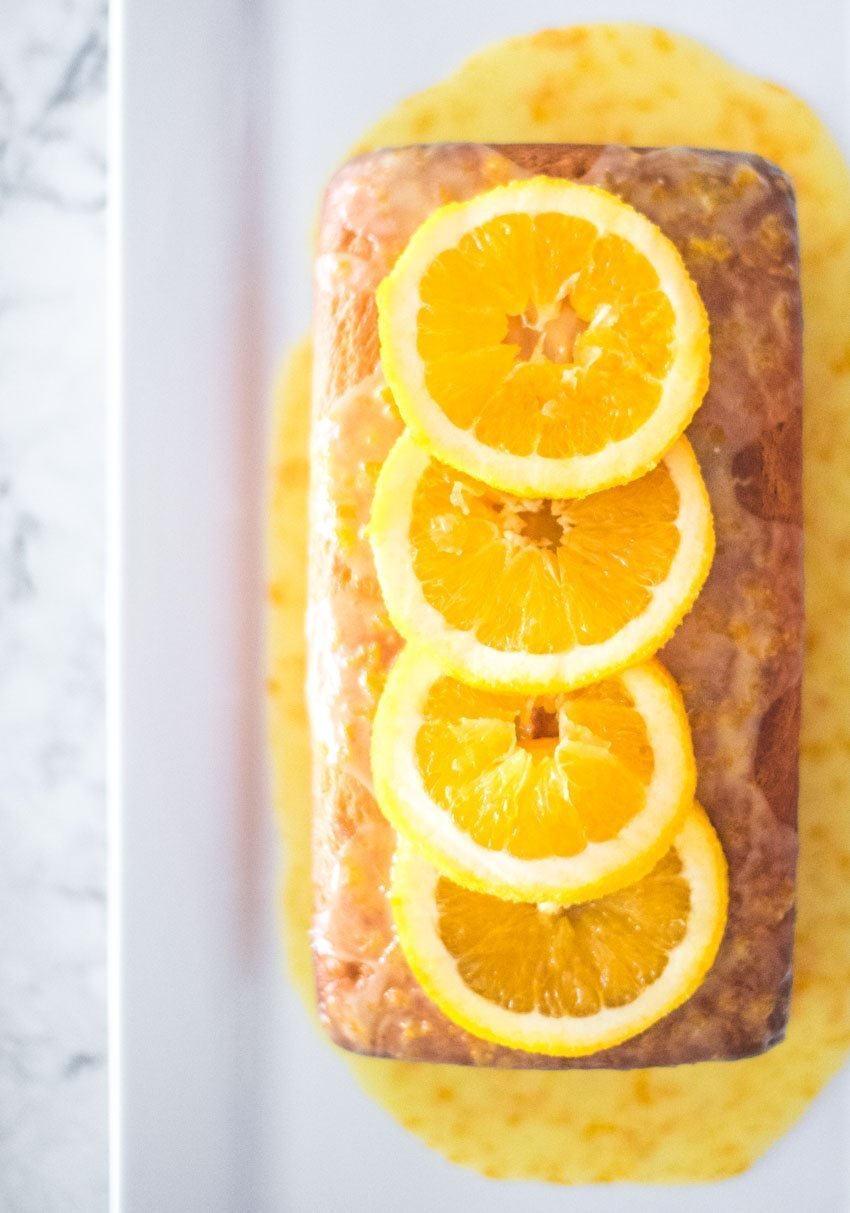 If you're on the lookout for a new dessert recipe to make this holiday season, feast your eyes on this Orange Yogurt Cake! We love it and know you will too! #orangeloafcake #orangeloafcakegreekyogurt #orangeloafrecipe #orangedessertrecipes