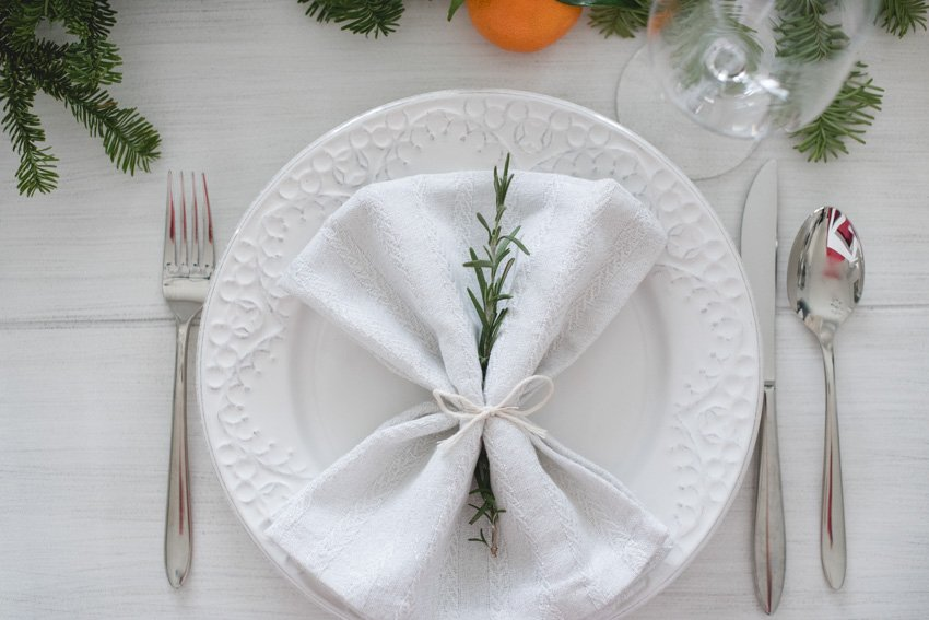 Looking for some holiday table setting inspiration? Here's an easy Christmas tablescape, using clementines and greenery, you can put together in no time! #christmastablescapes #christmastablesettings #holidaytablescapes #easychristmastabledecorations